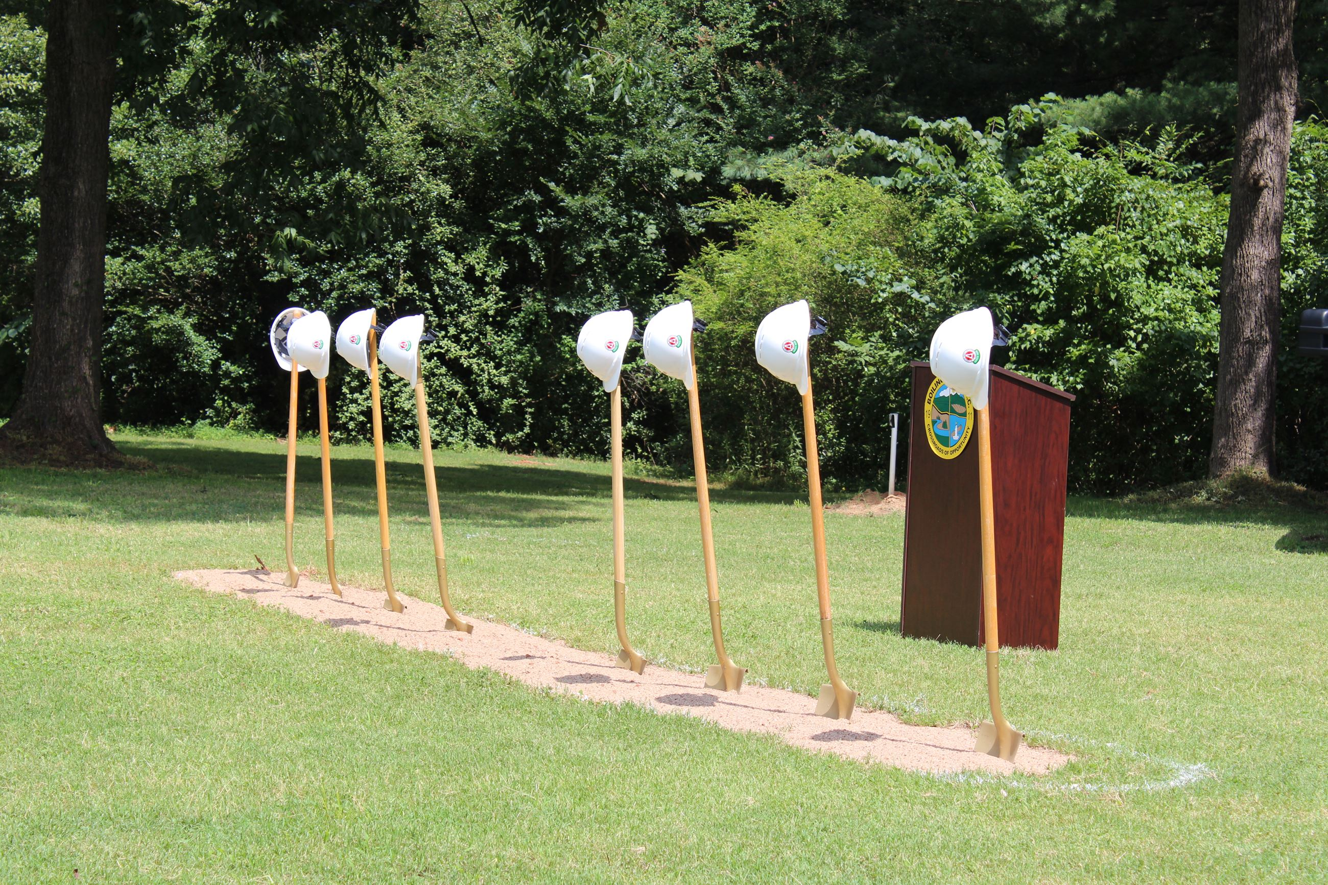 Row of golden shovels stuck in the ground.